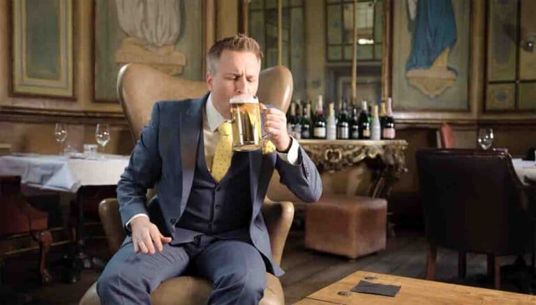 smartly dressed man drinking beer