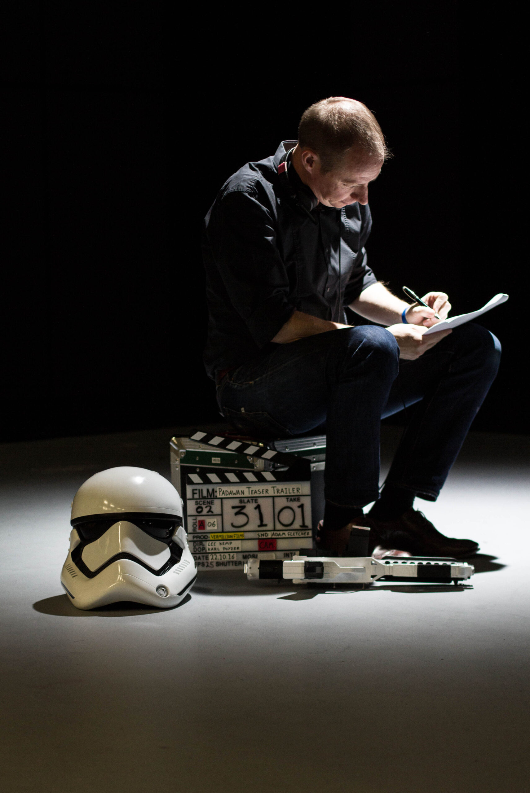 Lee sitting on a box by a stormtrooper helmet